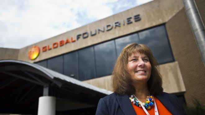 Janette Bombardier stands outside the entrance to the former IBM Essex Junction facility, which has a new bright orange GlobalFoundries logo. Bombardier will continue to head the facility.
