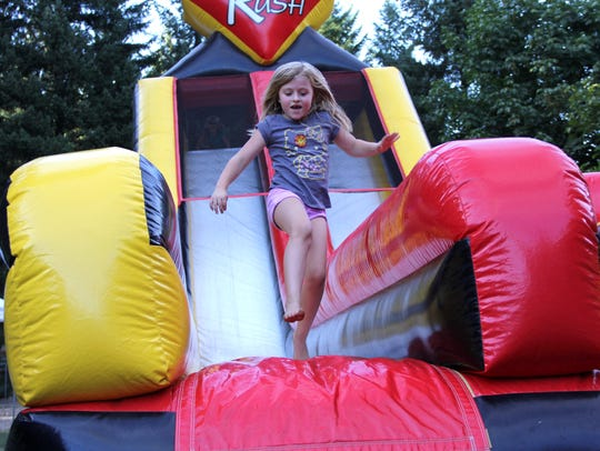 Amelia Sky slides down an inflatable slide at the Detroit
