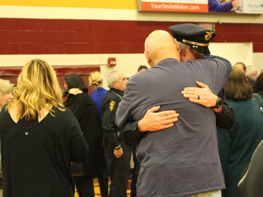 A Westerville police officer hugs a community member during a vigil at Westerville North High School, Sunday.