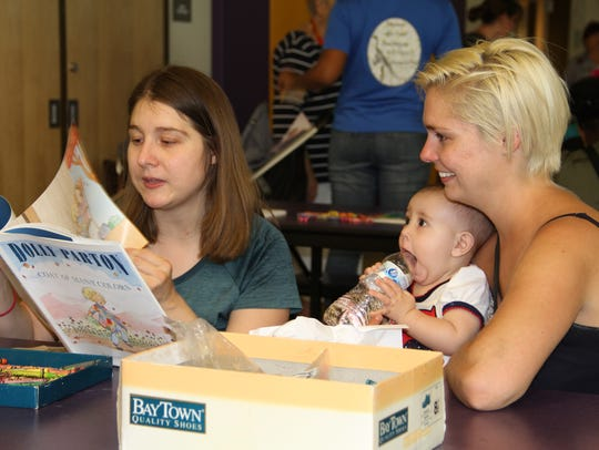 Mary Allen (L) reads to her daughter Amelia while Amelia's