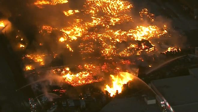 In this still image from video provided by KCBS News, flames and smoke billow from burning cardboard and wooden pallets at a recycling center in Ontario, Calif., Friday, Oct. 21, 2016. Fire crews in trucks and on nearby rooftops are pouring streams of water onto the blaze. No injuries have been reported. (KCBS News via AP)