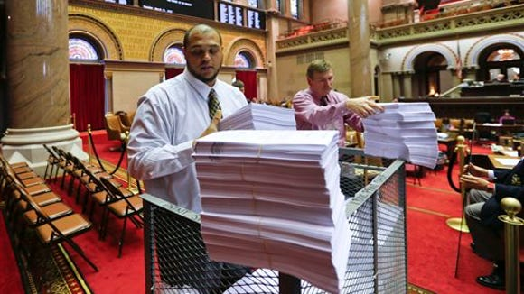 Lee Williams, left, and other workers unload budget bills in the Assembly Chamber at the Capitol on Tuesday, March 31, 2015, in Albany, N.Y.
