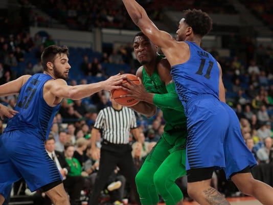 Oregon's Mikyle McIntosh, center, fights his way to the basket past DePaul 's Max Strus (31) and Eli Cain (11) in the first half of an NCAA college basketball game during the Phil Knight Invitational tournament in Portland, Ore., Friday, Nov. 24, 2017. (AP Photo/Timothy J. Gonzalez)