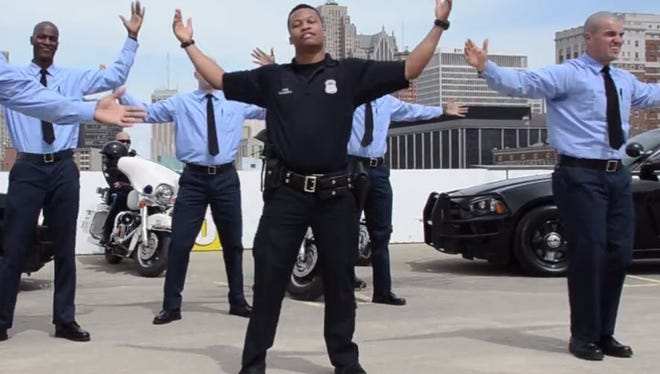 Detroit police officers dance as part of the Running Man Challenge in this Facebook screengrab.