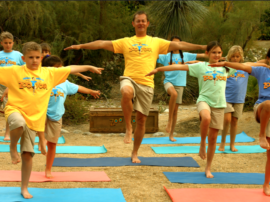 """Paduano (center) leads a group of children in an exercise routine during the filming of a TV pilot that accompanies his new children's book, """"Mikey-Mike's ZooYoga Party."""""""