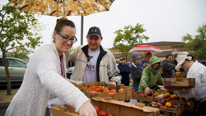 Jeannette Dube (accent over the e) and Ian Nunez shop early Saturday morning in the rain at Produce on Wheels-With Out Waste at Faith Bible Church in Glendale. Produce on Wheels-With Out Waste sells 60 pounds of fresh rescued produce for $10.