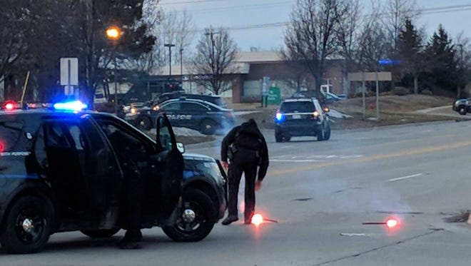 A police officer places flares Thursday afternoon at Cherry Hill and Canton Center roads in Canton Township, a short way from a bank where police said a robbery suspect was holding people hostage.