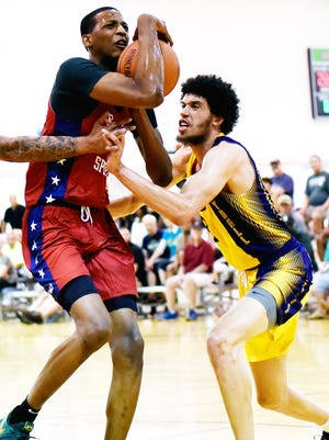 Trevor Manuel, right, pressures Marcus Bingham Jr. last week during a Moneyball Pro-Am summer league game. Manuel, once a big-deal recruit out of Lansing, will try to resurrect his basketball dreams next season at Olivet College.