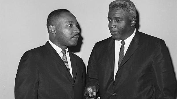 The Rev. Dr. Martin Luther King Jr. and Jackie Robinson talk before a press conference in 1962.