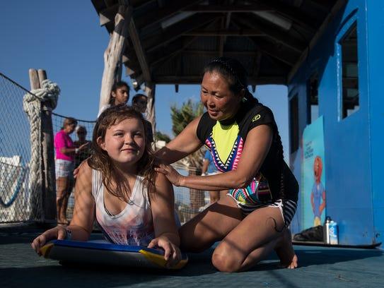 Cathy Seabertat teaches a Delaney Rye to surf at Schlitterbahn