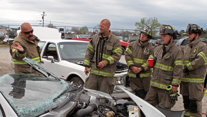 Montgomery County Fire and Rescue Service Training Captain Mark Chandler, left, leads  firefighters in extrication training Wednesday.