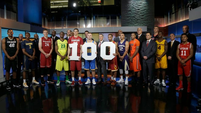 Players and coaches pose for photos while holding signs for the 100th anniversary of the Pac-12 conference during NCAA college basketball Pac-12 media day in San Francisco, Thursday, Oct. 15, 2015.