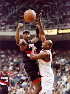 21 Feb 1997: Forward Clifford Robinson of the Portland Trail Blazers (left) passes the ball as Miami Heat player Isaac Austin covers him during a game at the Miami Arena in Miami, Florida. The Blazers won the game, 114-110.