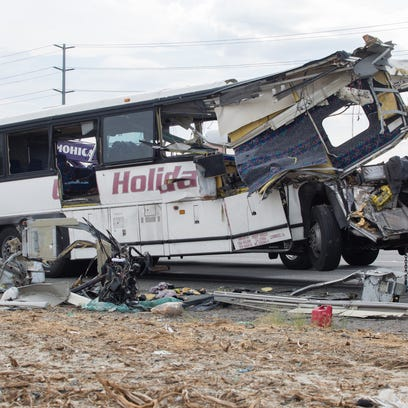 The wreckage of a tour bus is removed by workers on