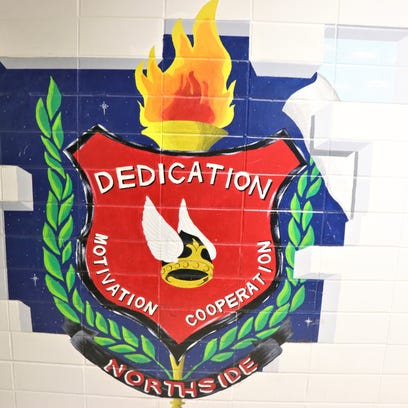 The Northside High School  motto is seen on a wall