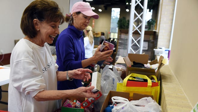 Volunteers Fran Carothers and Leslie Merritt make gift boxes for Operation Christmas Child at Venture Church in 2015. This year, shoeboxes will be collected during the third week in November.