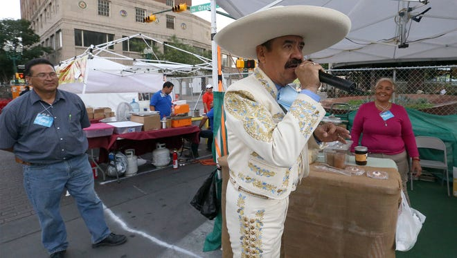 Gerardo Salas of Juárez speaks on a remote microphone as he samples the homemade salsas of Rosa Carbajal, right, in a booth called Your Health Therapy at the Mariachi Loco Music Festival on Saturday at San Jacinto Plaza in Downtown El Paso. Salas is the master of ceremonies for the three-day festival, which features a variety of mariachi and folklorico groups. Gates open at noon Sunday, the last day, with musical groups scheduled to perform throughout the afternoon and evening. Latin Grammy Award-winning ranchera singer Aida Cuevas is scheduled to finish the evening. Tickets are $15 for adults and $2 for children ages 12 and younger.