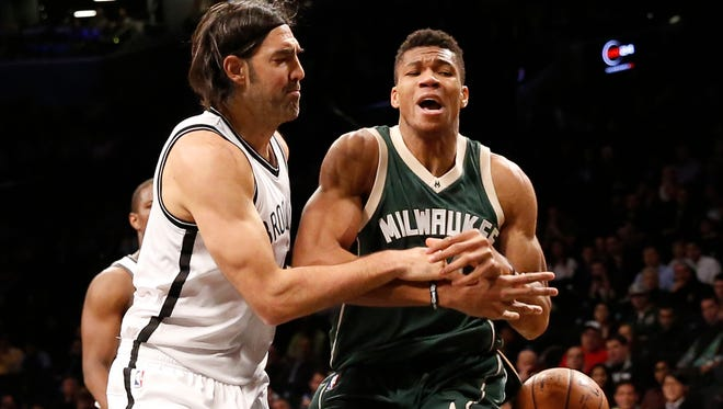 Milwaukee Bucks' forward Giannis Antetokounmpo (34) loses the ball as Brooklyn Nets' forward Luis Scola (4) gets tangled up with him in the first half on Thursday, Dec. 1, 2016, in New York.