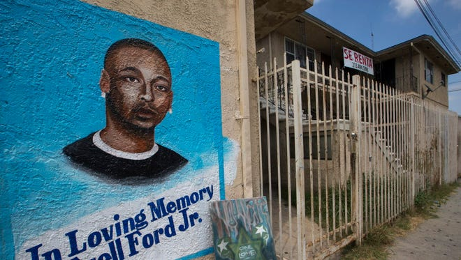 A mural and memorial for the late Ezell Ford Jr., who was fatally shot by Los Angeles police officers of in South Los Angeles, is seen on Monday, July 6, 2015. Police Chief Charlie Beck will have to take questions, in a formal deposition, from the attorney for the family of Ford, a federal judge ruled, citing contradictions between the chief's statements and a commission's finding that the shooting wasn't justified.