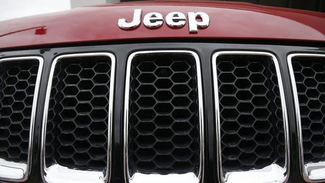 This Tuesday, Dec. 2, 2014 photo shows the Jeep logo on a Cherokee vehicle at a local car dealership in Tempe, Ariz.