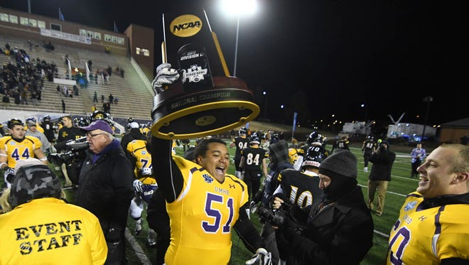 Mary Hardin-Baylor offensive lineman DeJuan Ramirez (51) celebrates with the Division III championship trophy on Friday.