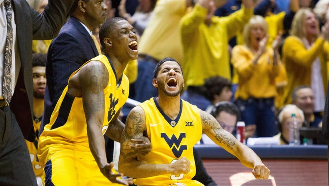 West Virginia guards Teyvon Myers (0) and James Bolden (3) celebrate late in the second half against Kansas.