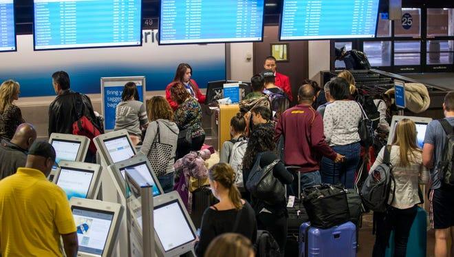 Travelers check in at American Airlines kiosks at Phoenix Sky Harbor November 24, 2015.