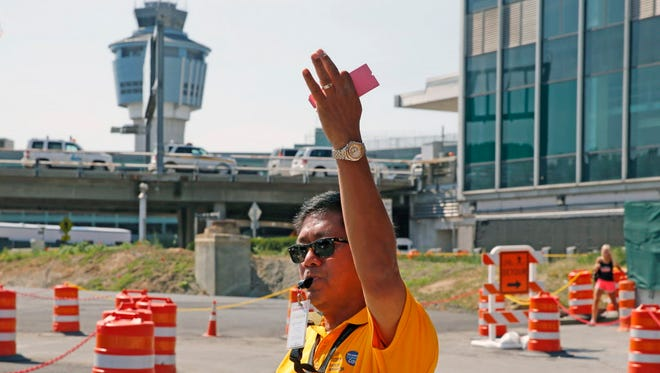 A Port Authority customer care representative directs traffic Aug. 24, 2016, during the $4 billion renovation project at LaGuardia Airport in New York. Demolition of an existing parking garage and the construction of two new ones has added to the normally busy airport's traffic congestion woes.