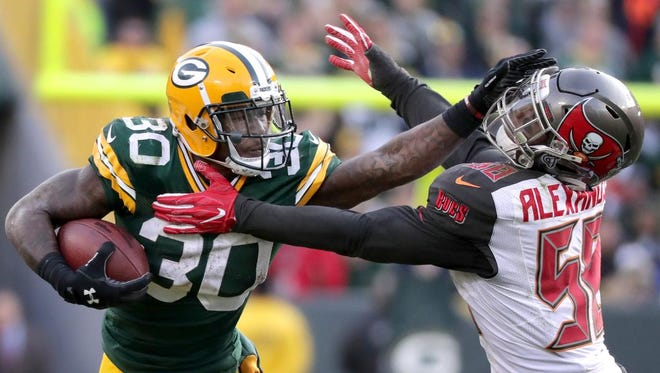 Green Bay Packers running back Jamaal Williams (30) stiff arms Tampa Bay Buccaneers middle linebacker Kwon Alexander (58) in overtime on December 3, 2017, at Lambeau Field in Green Bay, Wis. The Green Bay defeated Tampa Bay 26-20.