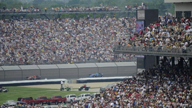 FILE - The crowd watches race cars run from turn three to four during the Indianapolis 500.