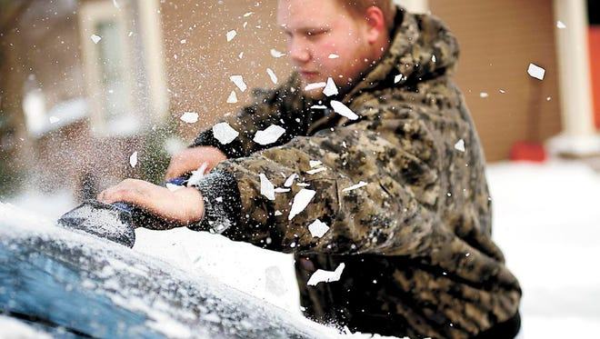 Brandon Kalenda scrapes ice off the back window of his car, Tuesday, April 1, 2014, in Fergus Falls, Minn. A spring blizzard that dumped heavy amounts of snow in parts of the Upper Midwest on Monday. (AP Photo/The Fergus Falls Daily Journal, Rian Bosse)