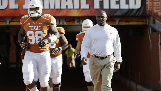 Texas coach Charlie Strong walks onto the field with his players before an NCAA game on Aug. 30 in Austin.