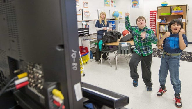 Sawyer Whitely, left, and Michael Mendoza, both 10 and autistic, play selected video games at Steuart W. Weller Elementary School in Ashburn, Va.