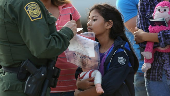 A Border Patrol officer records family information of Salvadorian migrants on July 24 in Mission, Texas.