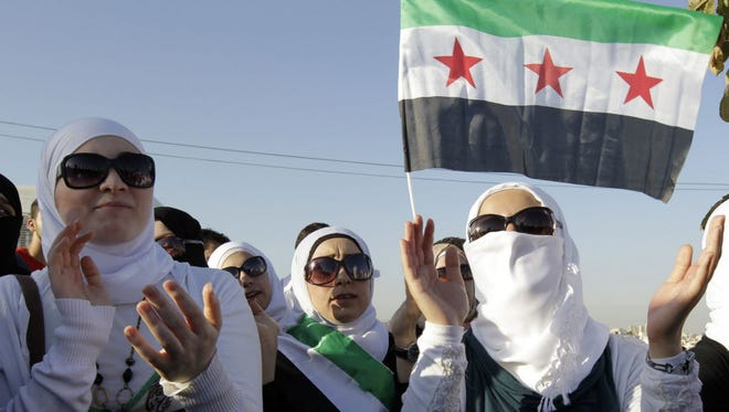 Syrians living in Jordan shouts slogans against Syrian President Bashar al-Assad during a rally outside of the Syrian Embassy in the capital Amman, on Aug. 21.