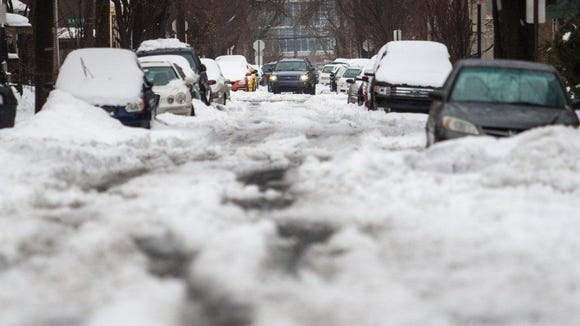 An SUV makes its way down a snow covered Jefferson Street near Eighth Street in Wilmington on Thursday afternoon, the day after nearly a foot of snow fell.
