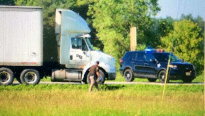 A Brown County Sheriff's officer works the scene of the accident on Wisconsin 29 in Howard on Monday morning.