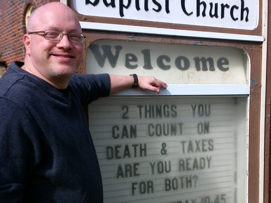 Park Avenue Baptist Church pastor Mike Brink, with the smaller sign in front of the building.