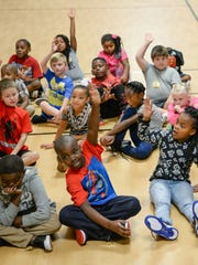 First and second grade students raise their hands to say learning is the most important reason they are in school, during orientation on the first day of school in Anderson School District 5 at Homeland Park Elementary in Anderson on Tuesday.