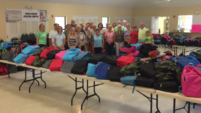 Volunteers stand with the filled backpacks the day before the annual giveaway last August at St. Luke's Episcopal Church in Port Salerno.
