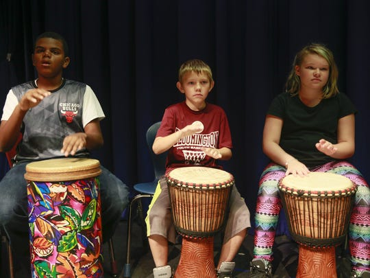 Students, from left, Nehemiah Dangerfield, Braden Quick and Joslyn Christie participate in a West African drumming circle in Bloomington, Ind. The unconventional approaches to elementary education that include violin, show choir, hip-hop dance and drumming are all part of Fairview Elementary's Artful Learning curriculum, and teachers and instructors at the school say it's paying off.