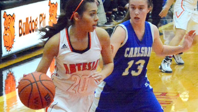 Artesia senior wing Mia Oliver looks to move the ball against Carlsbad junior guard Lauryn Wade in the second quarter Tuesday.