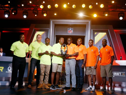 From left, John Randle, NFL Hall of Fame member and Team Carter Pro Bowl Alumni Co-Captain, Houston Texans Pro Bowl player J.J. Watt, Pittsburgh Steelers Pro Bowl player Antonio Brown, Cris Carter, NFL Hall of Fame member and Team Carter Pro Bowl Alumni Captain, Michael Irvin, NFL Hall of Fame member and Team Irvin Pro Bowl Alumni Captain, Darren Woodson, NFL Hall of Fame member and Team Irvin Pro Bowl Alumni Co-Captain, Cleveland Browns Pro Bowl player Joe Haden, and Dallas Cowboys Pro Bowl player DeMarco Murray, pose for photographers with the Pro Bowl Trophy during the Pro Bowl Kickoff news conference Tuesday, Jan. 20, 2015, in Phoenix. (AP Photo/Ross D. Franklin)