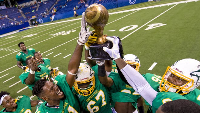 Kentucky State University players celebrate  their victory with the trophy. The 33rd Annual Circle City Classic pitted Ohio's  Central State University  against Kentucky State University on Saturday, Sept. 24, 2016, at Lucas Oil Stadium, in Indianapolis. After forcing the game into overtime, Kentucky State won   17-14.