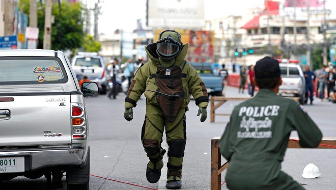 A Thai member of the Explosive Ordnance Disposal (EOD) wearing a bomb suit walks after defusing a suspicious object after two bombs exploded at the clock tower site in the center of Hua Hin city, Thailand, Aug. 12, 2016.