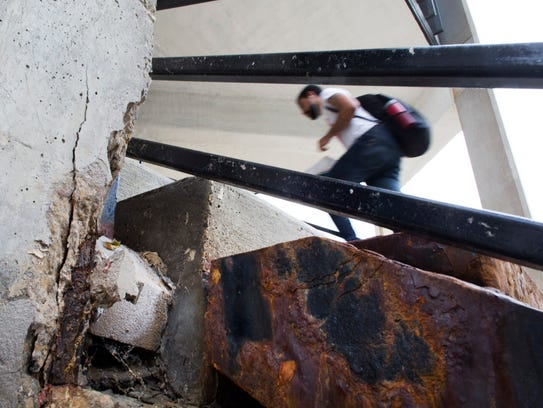 A man passes by crumbling concrete and exposed rebar