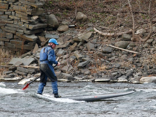 Steve Bush rides a stationary wave on the Chenango River with his stand up paddleboard in Chenango Forks on Monday, December 4, 2017.