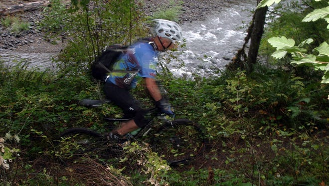 A cyclist rides the Salmon Creek Trail in Oakridge. The town is starting water restrictions.