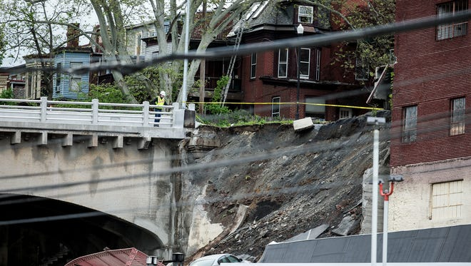A member of emergency crews looks at a collapsed retaining wall of the Mulberry Street bridge in Harrisburg, Pa., Thursday, May 5, 2016.