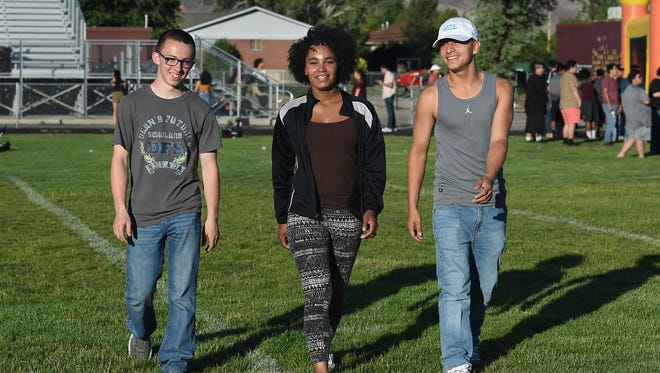 Neil Penrod, left, Elizabeth Long, center, and Justin Fuentes, share a laugh as they walk on the football field during Senior Sunset at Spark, High School. The three are 2018 Sparks High graduates. They were middle school students in 2013 when a classmate brought a gun to school and  killed a teacher, injured two students and killed himself.